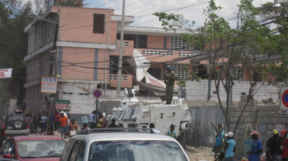 peruvian soldier on tank guarding haitians