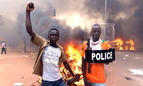 Protesters pose with a police shield outside the parliament in Ouagadougou on October 30, 2014 as cars and documents burn outside. Hundreds of angry demonstrators in Burkina Faso stormed parliament on October 30 before setting it on fire in protest at plans to change the constitution to allow President Blaise Compaore to extend his 27-year rule. AFP PHOTO / ISSOUF SANOGOISSOUF SANOGO/AFP/Getty Images