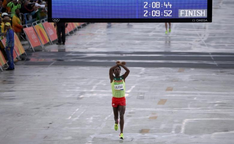 2016 Rio Olympics - Athletics - Final - Men's Marathon - Sambodromo - Rio de Janeiro, Brazil - 21/08/2016. Feyisa Lilesa (ETH) of Ethiopia celebrates as he wins silver REUTERS/Sergio Moraes