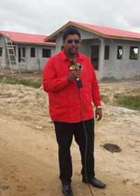 former minister of housing ifaan ali addressing the press next to a pile of cow dung